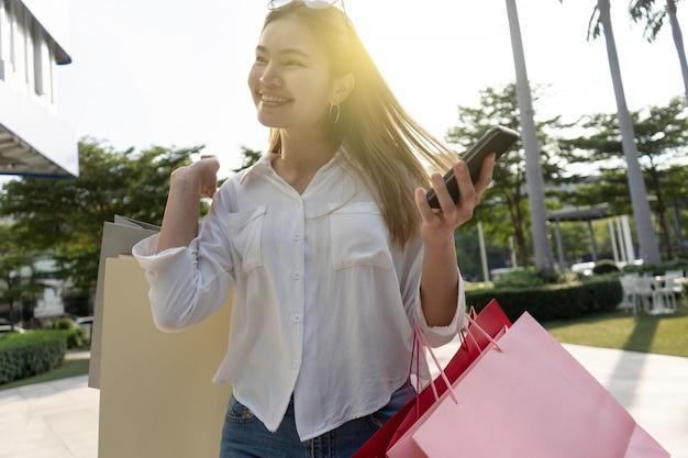Schönes mädchen mit langen haaren sie kauft glücklich im einkaufszentrum ein