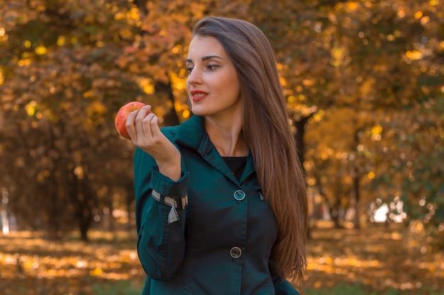 Schönes mädchen mit langen haaren steht im park schaut weg und hält apple in der hand