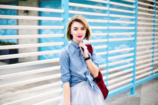 Schönes mädchen mit leuchtend rosa lippen und tätowierung auf ihrer hand, die smartphone mit blauen und weißen streifen auf dem hintergrund hält.