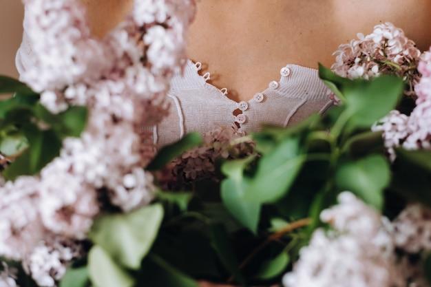 Schönes mädchen mit lila blumen in ihren händen. ein mädchen mit lila blumen im frühjahr zu hause. ein mädchen mit langen haaren und flieder in den händen.