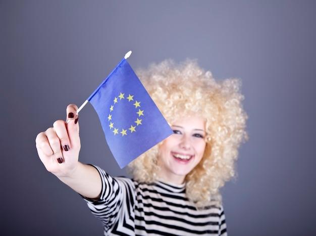 Schönes mädchen mit locken zeigen flagge der europäischen union.