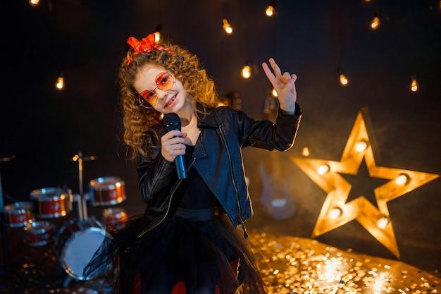 Schönes mädchen mit lockigem haar, das lederjacke und rote sonnenbrille trägt, singt in ein drahtloses mikrofon für karaoke im aufnahmestudio