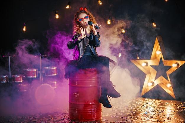 Schönes mädchen mit lockigem haar, das lederjacke und rote sonnenbrille trägt, singt in ein drahtloses mikrofon