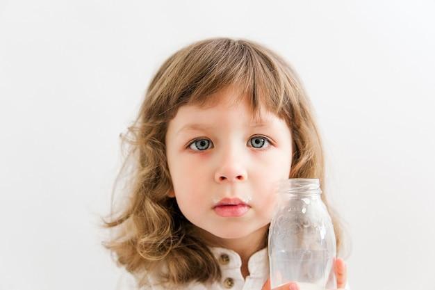 Schönes mädchen mit lockigem haar und blauen augen trinkt milch von einer flasche.
