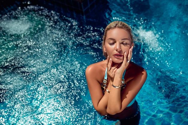 Schönes mädchen mit modeaccessoires genießt ihren urlaub, der im pool steht und ihre augen schließt.