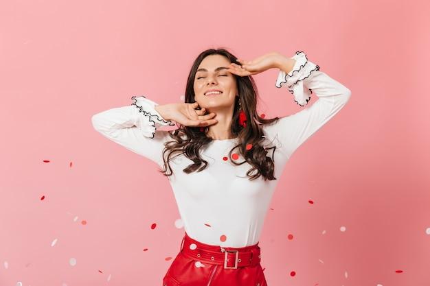 Schönes mädchen mit noppenwangen lächelt. frau im stilvollen outfit schlägt auf rosa hintergrund.