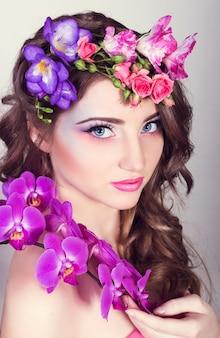 Schönes mädchen mit orchideen und freesien im haar