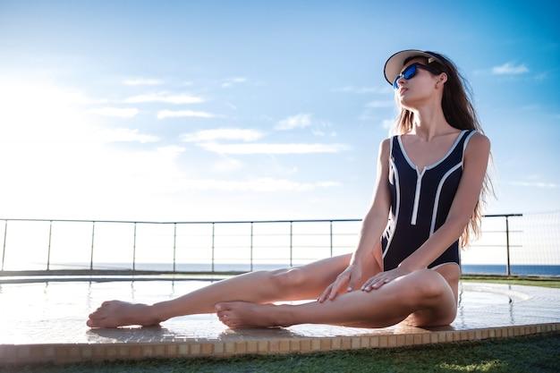 Schönes mädchen mit perfekt gegerbtem körper im blauen badeanzug