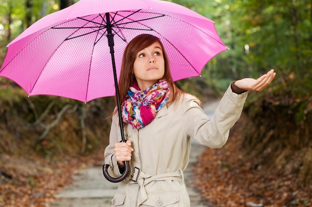 Schönes mädchen mit regenschirm, der für regen prüft