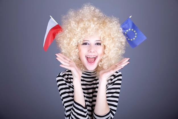 Schönes mädchen mit ringeln zeigt flagge der europäischen union und polens.