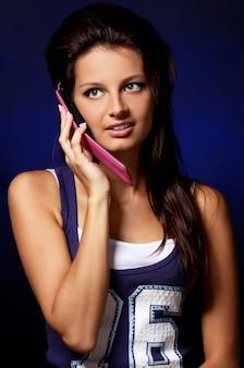 Schönes mädchen mit rosafarbenem mobiltelefon