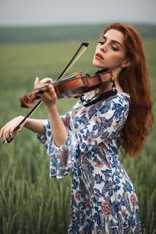Schönes mädchen mit rotem haar und blauem kleid, das geige auf naturfeld der blumen hält.
