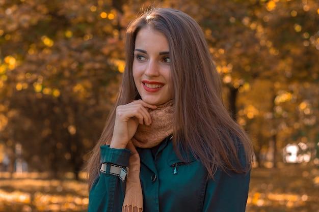 Schönes mädchen mit rotem lippenstift steht im herbstpark und lächelt nahaufnahme
