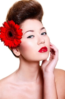 Schönes mädchen mit roten lippen und nägeln mit einer blume auf ihrem haar
