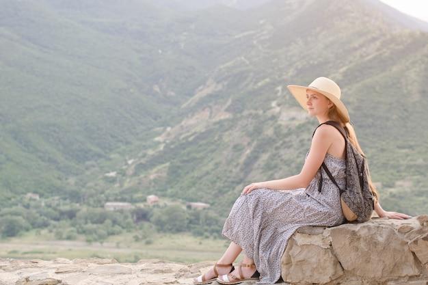 Schönes mädchen mit rucksack in einem breiten hut, der auf bergen sitzt