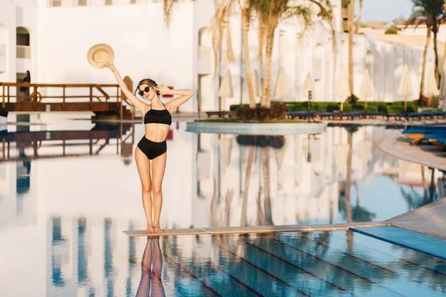 Schönes mädchen mit schlankem körper, modell, das schwarzen badeanzug trägt, der in der mitte des pools im luxushotel, resort aufwirft. urlaub, ferien, sommerzeit.