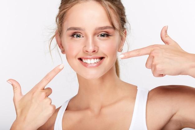 Schönes mädchen mit schneeweißen zähnen auf weißem studiohintergrund, zahnmedizinkonzept, perfektes lächeln, auf zähne zeigend.