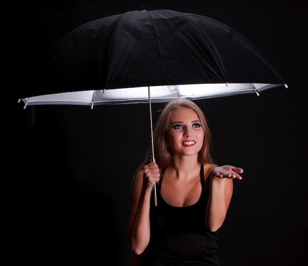 Schönes mädchen mit schwarzem regenschirm auf schwarzem hintergrund