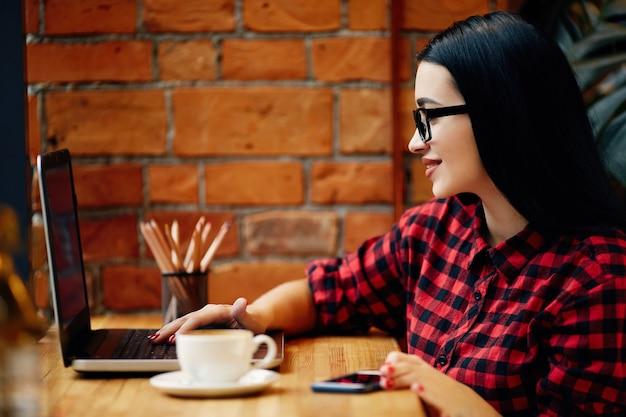 Schönes mädchen mit schwarzen haaren, die brillen tragen, die im café mit laptop und tasse kaffee sitzen, freiberufliches konzept, porträt, rotes hemd tragend.