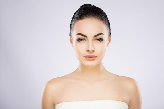 Schönes mädchen mit schwarzen haaren, großen augen, dicken augenbrauen und nackten schultern in grau, ein modell mit hellem nacktem make-up.