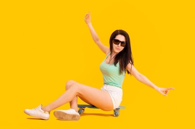 Schönes mädchen mit sonnenbrille, die auf einem skateboard sitzt