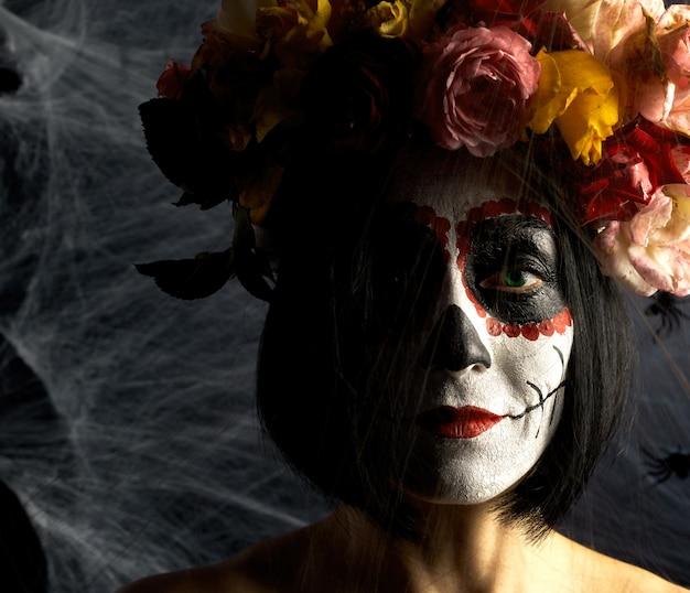 Schönes mädchen mit traditioneller mexikanischer totenmaske. calavera catrina