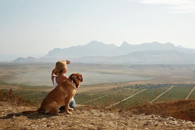 Schönes mädchen mit und hund auf dem berggipfel