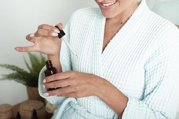 Schönes mädchen mit vitiligo lächelt mit feuchtigkeitsspendendem serum. schließen sie eine pipette von einer pipette