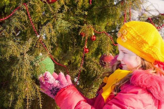 Schönes mädchen mit weihnachtsbaum im winterpark