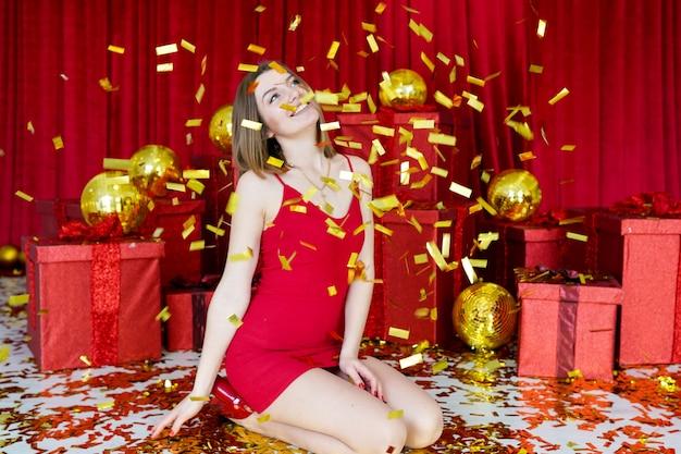 Schönes mädchen mit weihnachtsgeschenken lächelt ein schönes lächeln