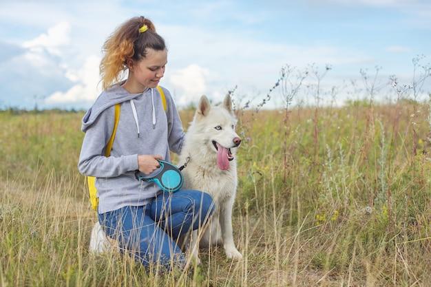 Schönes mädchen mit weißem hund, teenager, der mit husky haustier geht