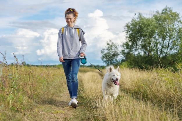 Schönes mädchen mit weißem hund, teenager, der mit husky haustier, hintergrundlandschaft mit bewölktem himmel, gelbem verbranntem gras geht