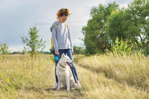 Schönes mädchen mit weißem hund, teenager, der mit husky haustier, raumlandschaft, gelbes verbranntes gras geht
