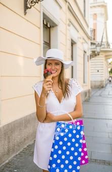 Schönes mädchen mit weißem hut und einkaufstaschen eiscreme auf stadtstraße essend