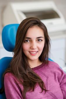 Schönes mädchen mit zahnspangen lächelt in der zahnmedizin