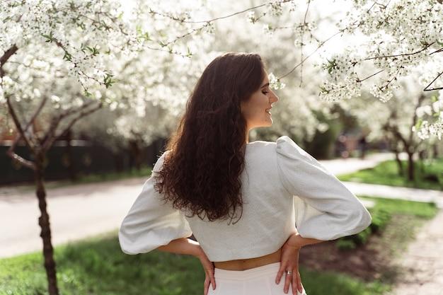 Schönes mädchen nahe blühenden bäumen im park. gehen im freien an sonnigem tag. lebensstil der jungen frau.