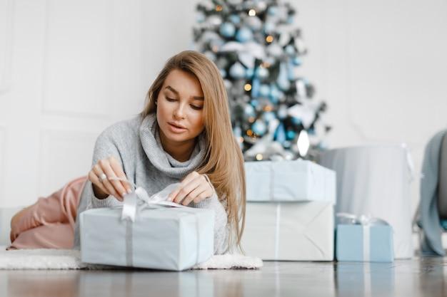 Schönes mädchen nahe dem weihnachtsbaum ist von geschenken umgeben, packt geschenke aus