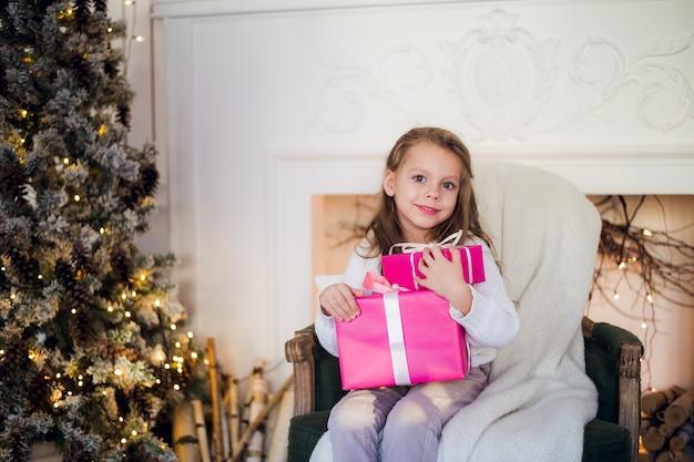 Schönes mädchen nahe weihnachtsbaum, das geschenke auspackt, die auf einem stuhl sitzen