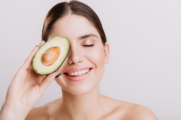 Schönes mädchen ohne make-up, das mit geschlossenen augen auf weißer wand aufwirft. das lächelnde modell bedeckt das gesicht mit einer gesunden avocado.