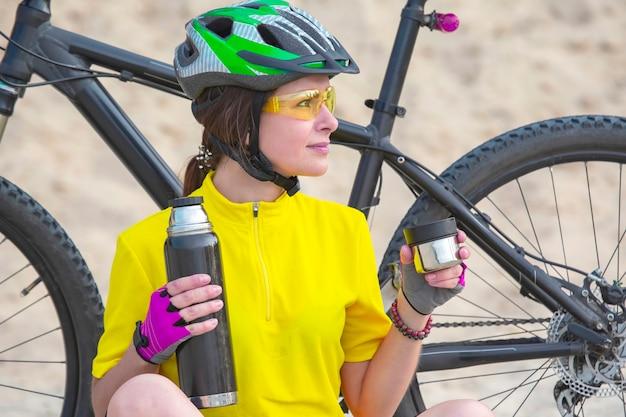 Schönes mädchen radfahrer in gelb mit tee und thermoskanne in der hand auf dem hintergrund des sandes. sport und erholung. natur und mensch