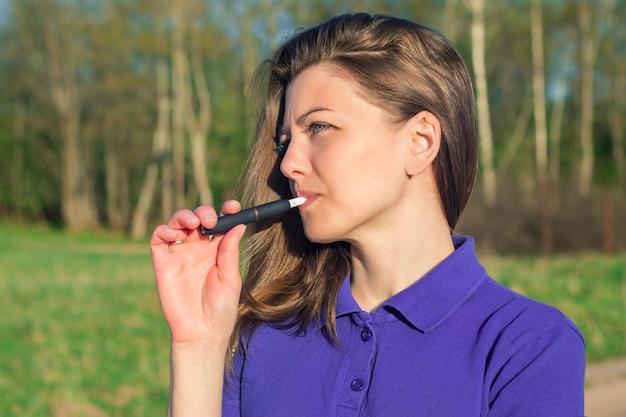 Schönes mädchen raucht modernes hybrides elektronisches zigarettengerät, technologie, erhitzen des neuen tabaksystems, puff. gesunde sicherheitsalternative zum rauchen. gesundheitswesen. junge frau, frau im freien