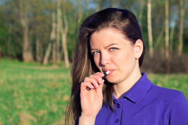 Schönes mädchen raucht modernes hybrides elektronisches zigarettengerät, technologie, neues tabaksystem erhitzend. gesunde sicherheitsalternative zum rauchen. gesundheitswesen. attraktive junge frau, weiblich im freien