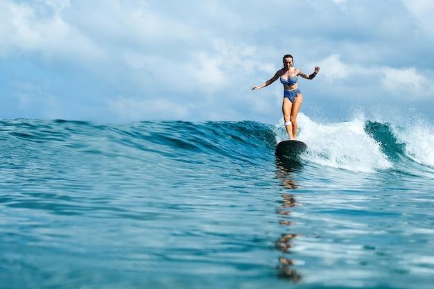 Schönes mädchen, reiten auf einem surfbrett auf den wellen