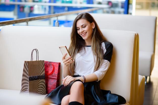 Schönes mädchen schaut auf das telefon in einem einkaufszentrum.
