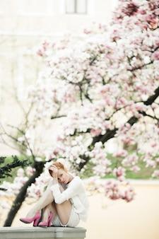 Schönes mädchen sitzt am geländer nahe dem erstaunlichen magnolienbaum