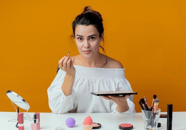 Schönes mädchen sitzt am tisch mit make-up-werkzeugen, die make-up-pinsel und lidschatten-palette halten, die lokal auf orange wand schauen