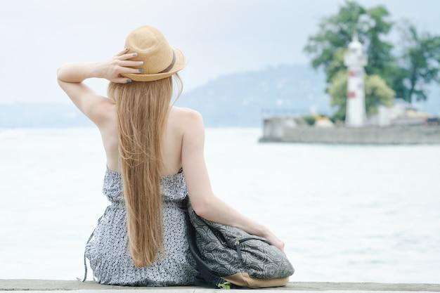 Schönes mädchen sitzt auf dem pier. das meer und der kleine leuchtturm in der ferne. rückansicht