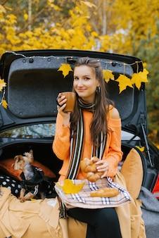 Schönes mädchen sitzt im kofferraum eines schwarzen autos mit ihrem hund und trinkt tee zum mittagessen auf einem herbsthintergrund.