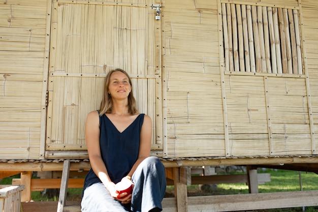 Schönes mädchen sitzt in der nähe des bungalows und trinkt kaffee.