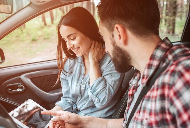 Schönes mädchen sitzt mit ihrem freund im auto und schaut auf den bildschirm. sie hält mit geschlossenen augen und lächelnd die hand am hals. sie sieht glücklich aus.
